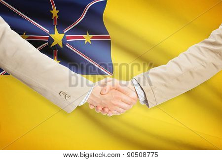 Businessmen shaking hands with flag on background - Niue poster