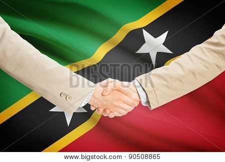 Businessmen shaking hands with flag on background - Saint Kitts and Nevis poster