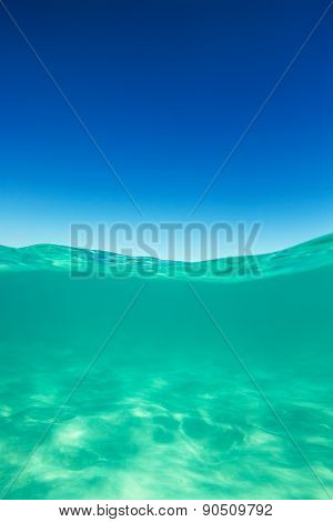 Clear Waterline Caribbean Sea Underwater And Over With Blue Sky Horizon