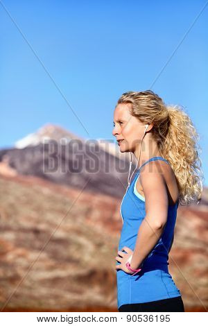 Running earphones - woman runner listening to music in earbuds. Female athlete portrait after running in beautiful nature. Healthy lifestyle concept with beautiful young blonde fitness model.