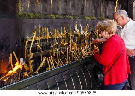 Sao Bento da Porta Aberta, Portugal. April 06, 2015: Pilgrims burning votive candles as fulfillment of vows. Pope Francis promoted the Sanctuary to Basilica in the 400th anniversary, March 21st