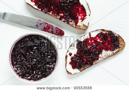 Diet healhty breakfast. Wholegrain toast with butter and jam on white kitchen table background