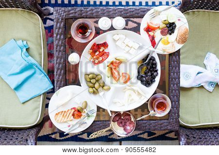 Unfinished Turkish breakfast on a patio table with a serving of fried eggs with a selection of fresh tomato olives cheese and mugs of Turkish tea overhead view with napkins on chairs poster