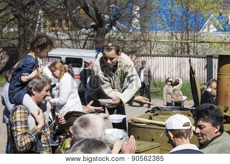 Mstyora,Russia-May 9,2015: Teenager In Oversea Cap Superimposes Porridge From Field Kitchen