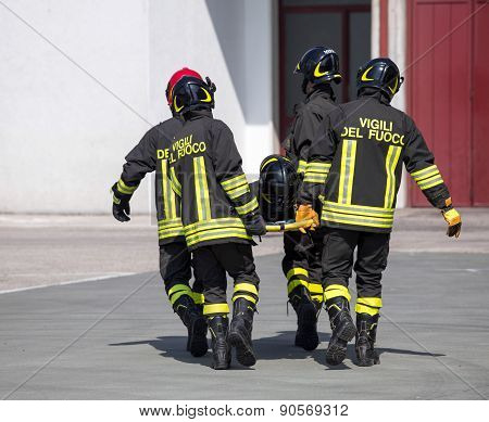 Four brave Firefighters carry a fellow firefighter with the stretcher poster