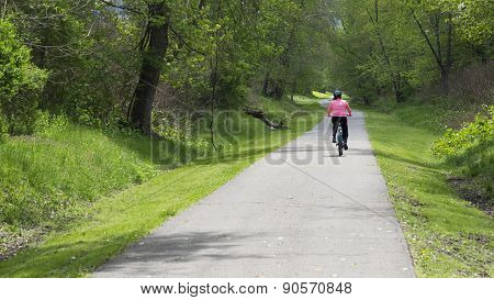 Woman Bicyclist on Trail with Green Tree, Watercress and Shrub Foliage.
