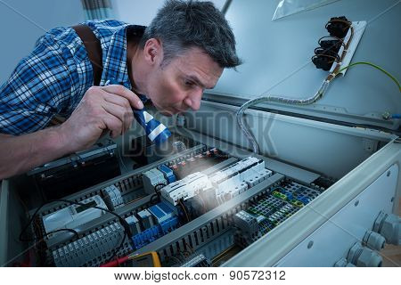 Electrician Analyzing Fusebox With Torch