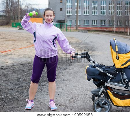 Young Woman Combines Sport And A Walk With Baby