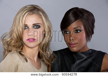 beautiful young african woman with pixie hair and european model with curly hair on studio background