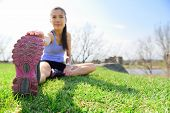 Fit fitness woman doing stretching exercises outdoors on grass. Girl doing hamstring leg stretching exercise and stretches. Female sports model exercising outdoor in summer. Beautiful Asian girl. poster