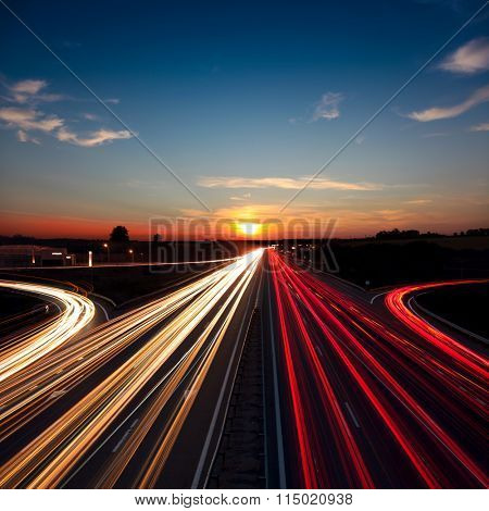 Speed Traffic light trails on motorway highway at sundown, long exposure, urban background with sun and dark sky