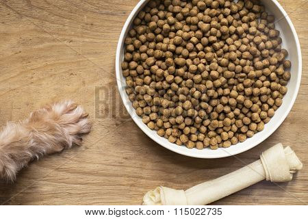 Dog Food And Dog Paw On Wood Table