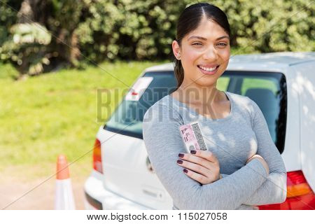 happy learner driver holding her driver's license