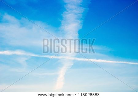 Cross contrails over blue sky background