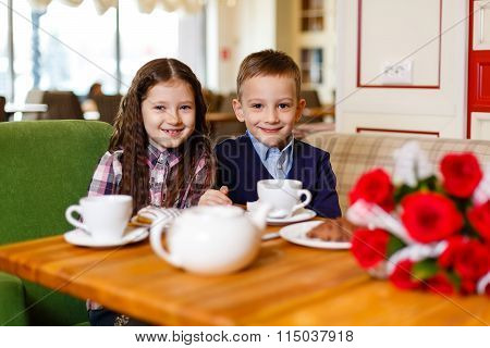 little girl with a baby boy , sitting at the table and drank tea with Cake