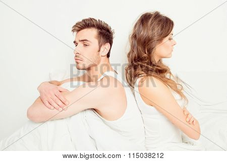 Young disconnected couple with problems sitting on the bed poster