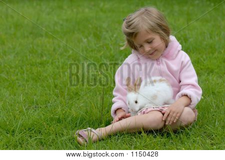 little girl with a rabbit on the grass poster