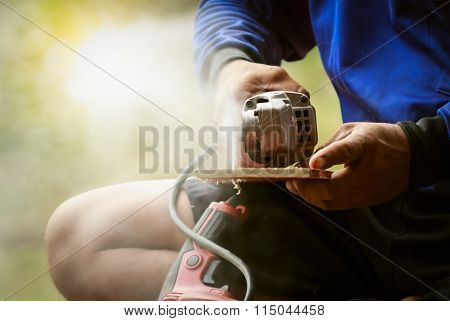 carpenter man sawing wood with electric saw