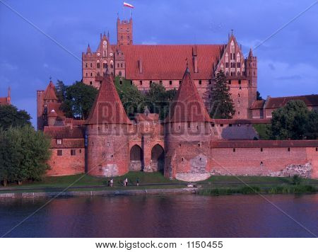 A Castle By The River At Dusk