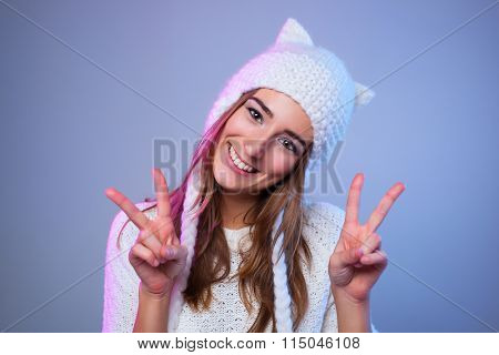 Young happy smiling woman showing victory sign. Warm winter white clothing.