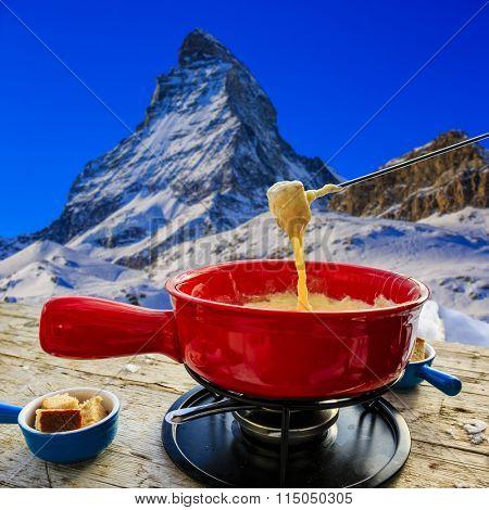 Fondue, traditional Swiss dish - Matterhorn in Swiss Alps in background