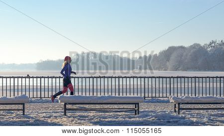 Young Woman Running In Winter Snow