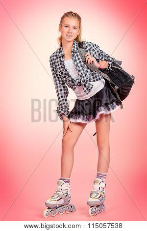 Full length portrait of a modern teen girl in roller skates posing over pink background.