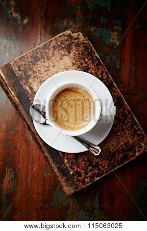 Cup of coffee on an old book