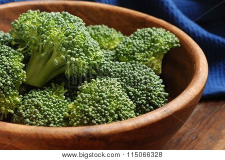 Fresh organic broccoli florets - (uncooked) -  in wooden bowl on rustic table.  Closeup with shallow dof.