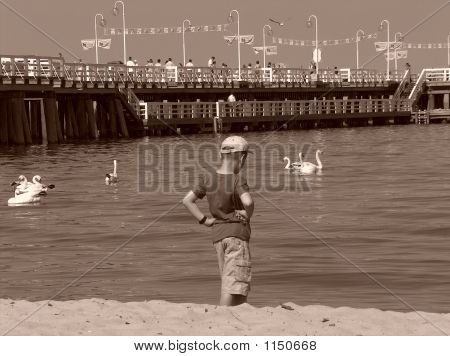 A Boy Standing By The Sea, Looking Into The Water Surface