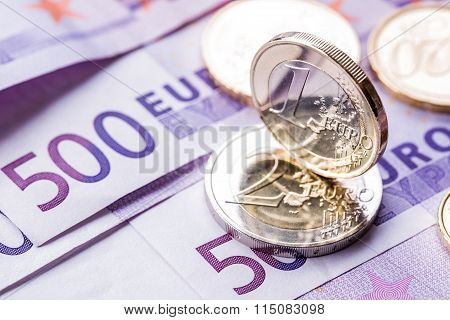 Several 500 euro banknotes and coins are adjacent. Symbolic photo for wealt.Euro coin balancing on s