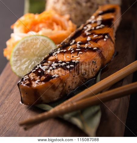 Teriyaki salmon with rice on a wooden platter. Top view.