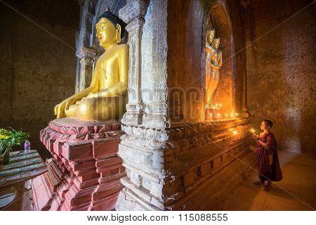 Unidentified Buddhism neophyte prays to the Buddha in Buddihist temple