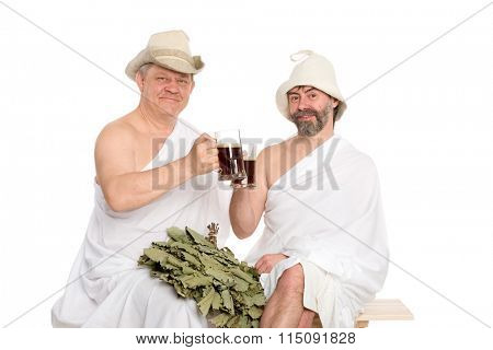Friends in traditional bathing costumes drink kvas - russian bread juice. From a series of Russian bath