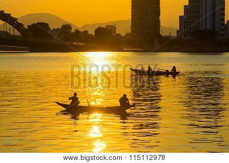 Fishermen on boat in Han river near Dragon River Bridge ( Rong Bridge) in sunset in Da Nang, Vietnam