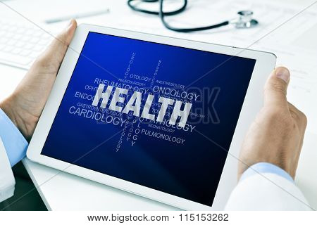 closeup of a doctor man sitting at his office desk holding a tablet computer with a tag cloud about health in its screen