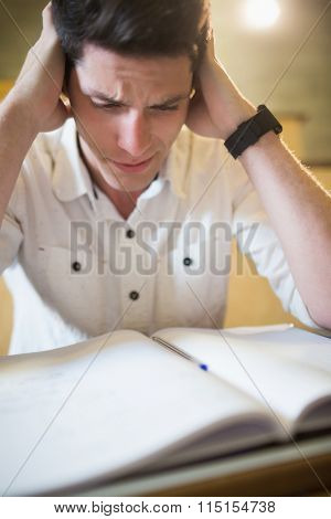 Anxious male student during exam in lecture hall