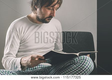 Man Reading Magazine Early In The Morning, Wearing Pajamas