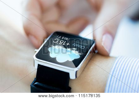 close up of hands with weather icon on smartwatch