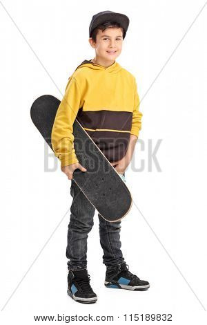 Full length portrait of a little boy holding a skateboard and looking at the camera isolated on white background