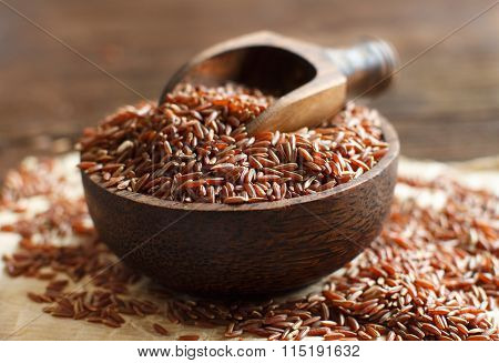 Uncooked Red Rice In A Bowl With A Wooden Spoon