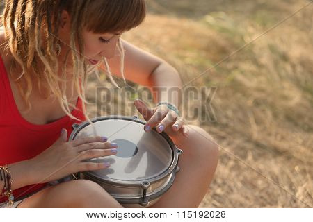 Females hands play a drum, close up
