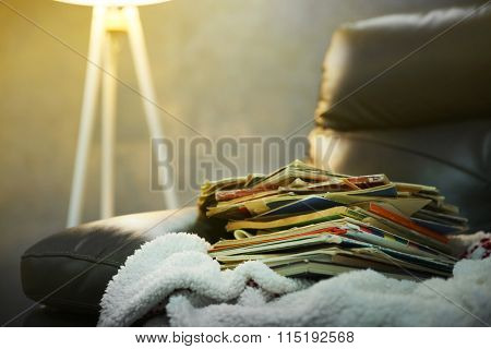 Pile of books on leather chair in the room, close up