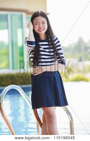 Portrait Of Asian Teen Age Smiling Face Standing In Home Swiming Pool With Relax And Happy Emotion