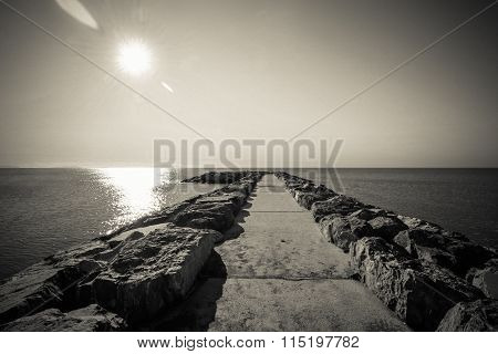 Black And White Nostalgic Tranquil Seascape Panorama With Stony Pier And Horizon Line.