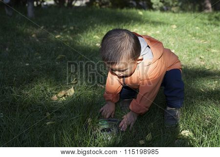 Cute Chinese Baby Boy Studying A Fountain Blow Hole In Grass