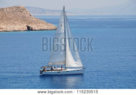 HALKI, GREECE - JUNE 14, 2015: A yacht sails out of Emborio harbour on the Greek island of Halki. The small island near Rhodes is a popular destination for the yachting community.