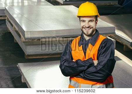 Smiling Worker In Protective Uniform In Front Of Sheet Tin Metal
