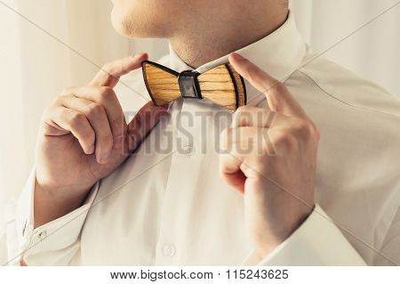 Groom Holding Wooden Bow-tie On Wedding Day