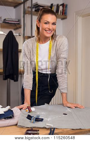 Portrait of young tailor woman leaning over table with sewing equipment. Happy fashion designer posing in her new shop and looking at camera.